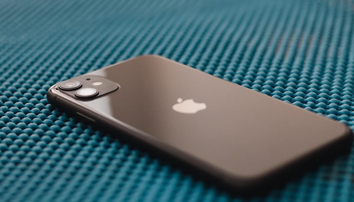Mobilní telefon iPhone 11 položený na stole.