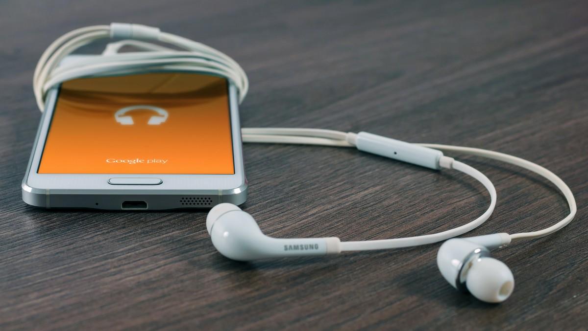 Podcasting provozovaný na mobilním telefonu se sluchátky.