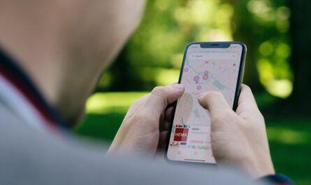 Mladík na mobilním telefonu využívá aplikaci Mapy.cz.